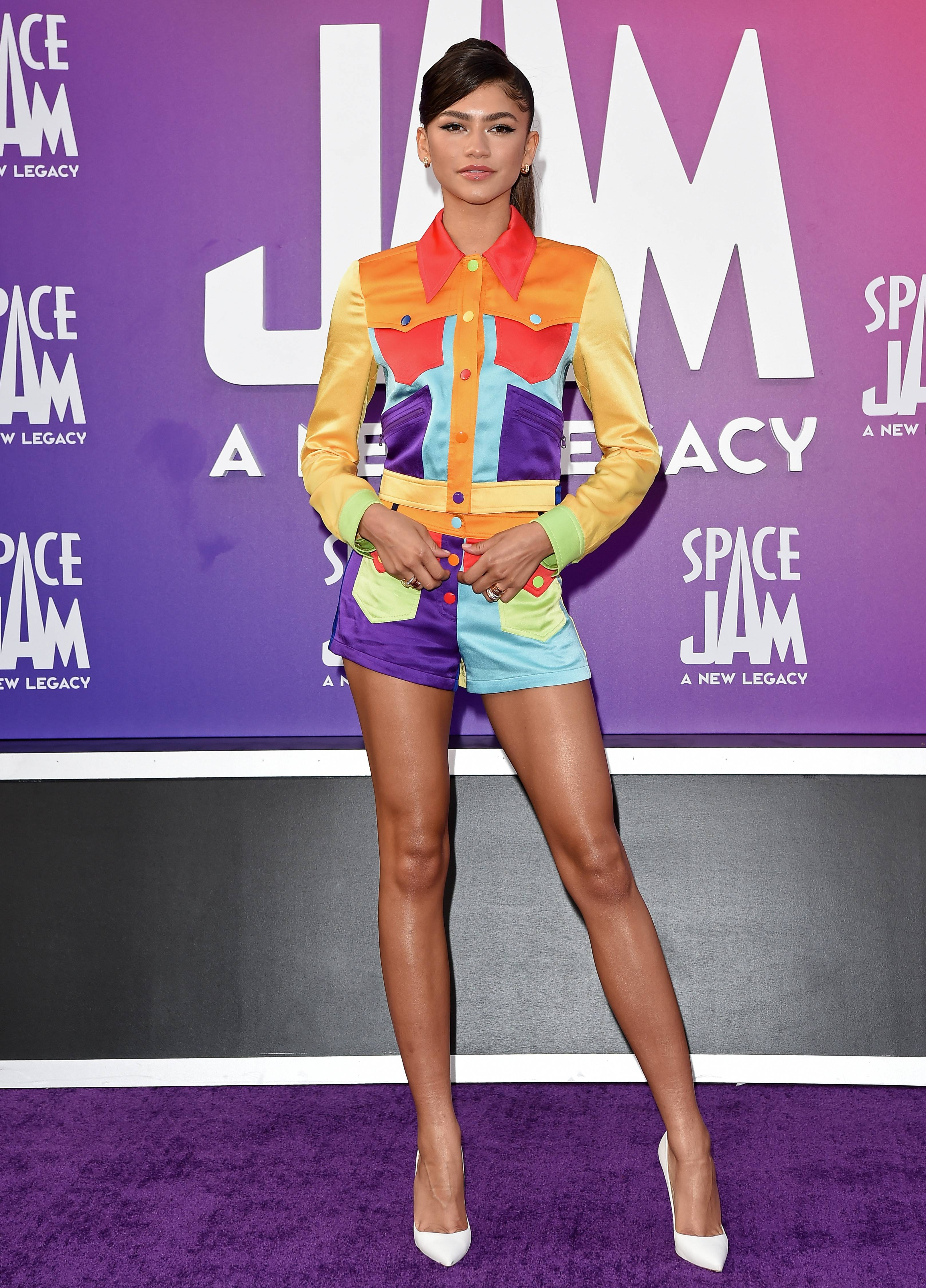 """Lola Bunny - Zendaya is a whole mood. The young actress attended the premier of """" Space Jam: The New Legacy"""" in which she plays the iconic Lola Bunny. Zendaya channeled the character on the red carpet rocking a fun, colorful shorts set. The look consisted of a colorblocked jacket and matching shorts from Moschino's Resort 22 collection. Zendaya accessorized with white Christian Louboutin pumps, as well as gold huggie hoop earrings and stacked rings by Bulgari. Though she didn't wear it for the entirety of the red carpet, she also had in tow a blue face mask with a sparkly basketball on it, which was actually made by her mom, Claire Stoermer. """"Mask courtesy of my mama,"""" she wrote on Instagram Stories.We are loving her look!"""