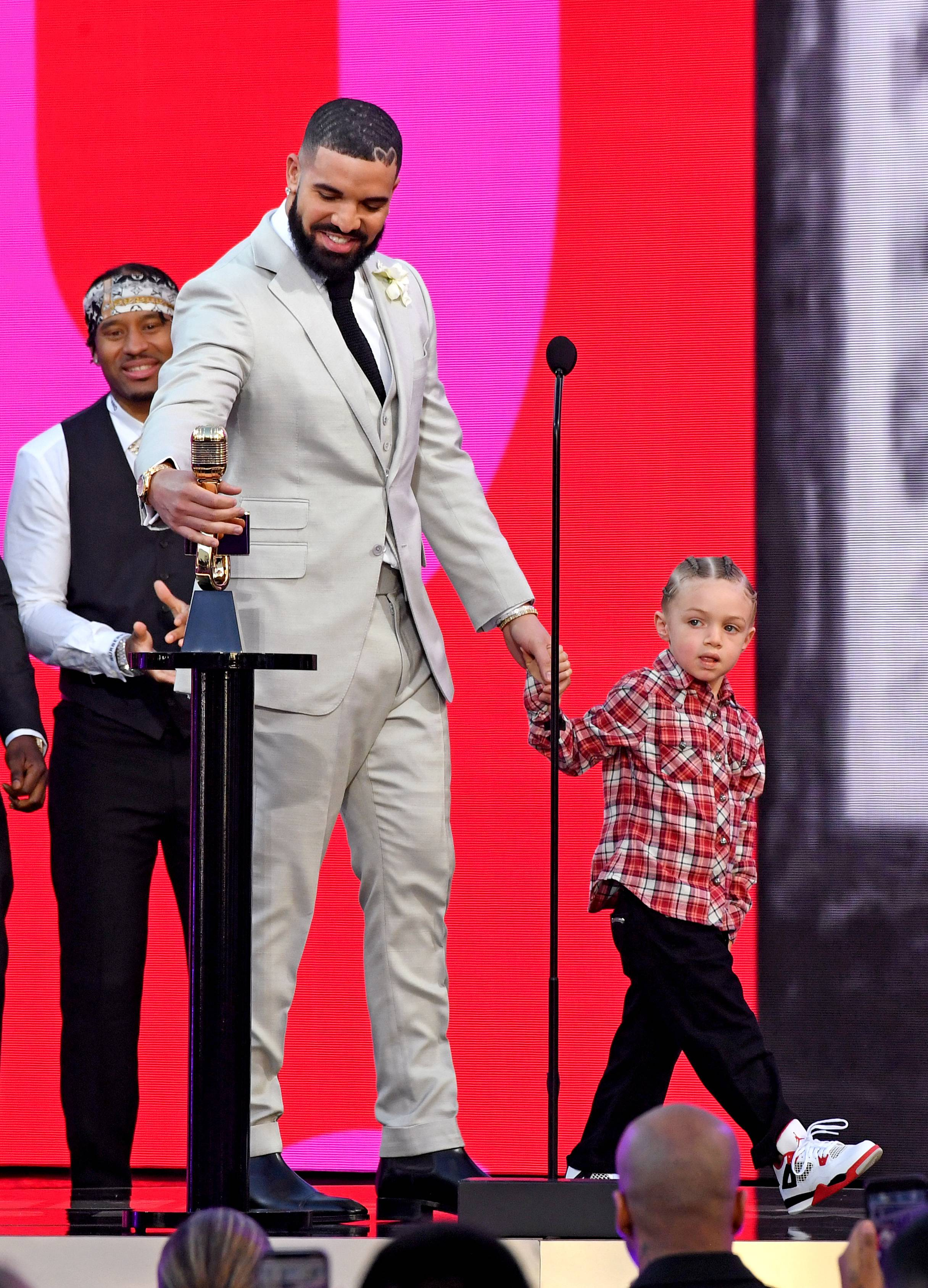 Drake And Adonis Graham - Drake's sonAdonis(3)caused quite a stir at the 2021 Billboard Music Awards with his fresh new kicks and neatly styled cornrows. We love that the legendary rapper and the 'Artist Of The Decade' recipient shared the monumental moment with his baby boy. So sweet!(Photo by Kevin Mazur/Getty Images) (Photo by Kevin Mazur/Getty Images)