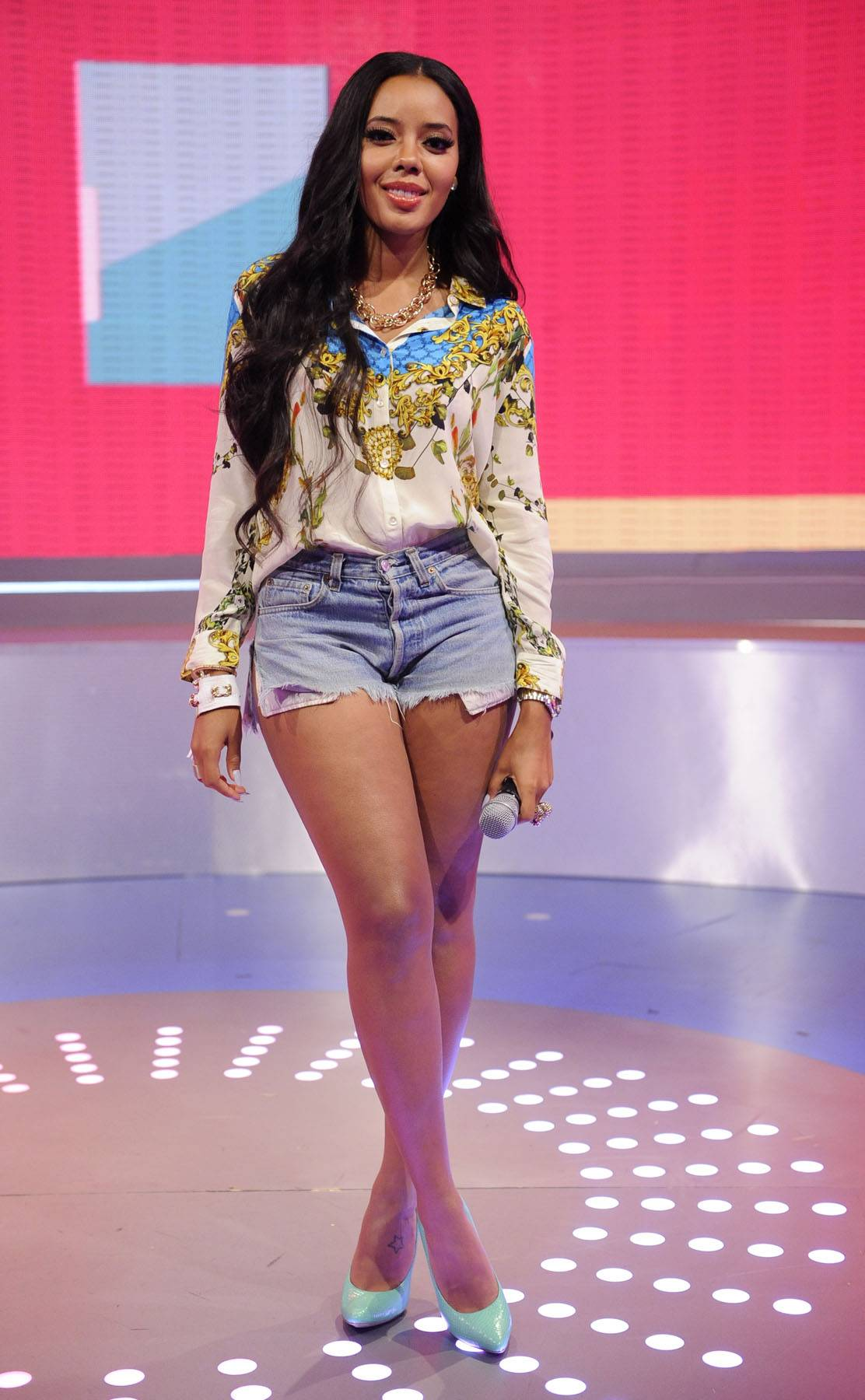 Long Hair, Don't Care - A beautifully embellished silk top with jean shorts and aqua pumps kept Angela's outfit dressy casual and could easily turn her day look into something for the night. (Photo: John Ricard/BET/Getty Images for BET)