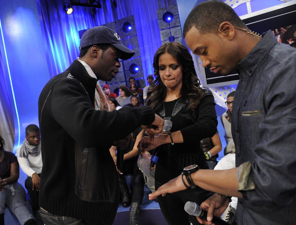 """Check This Out - Pras assists Rocsi Diaz in putting on her """"Embrace Haiti"""" bracelet at 106 & Park, January 12, 2012. (Photo: John Ricard / BET)"""