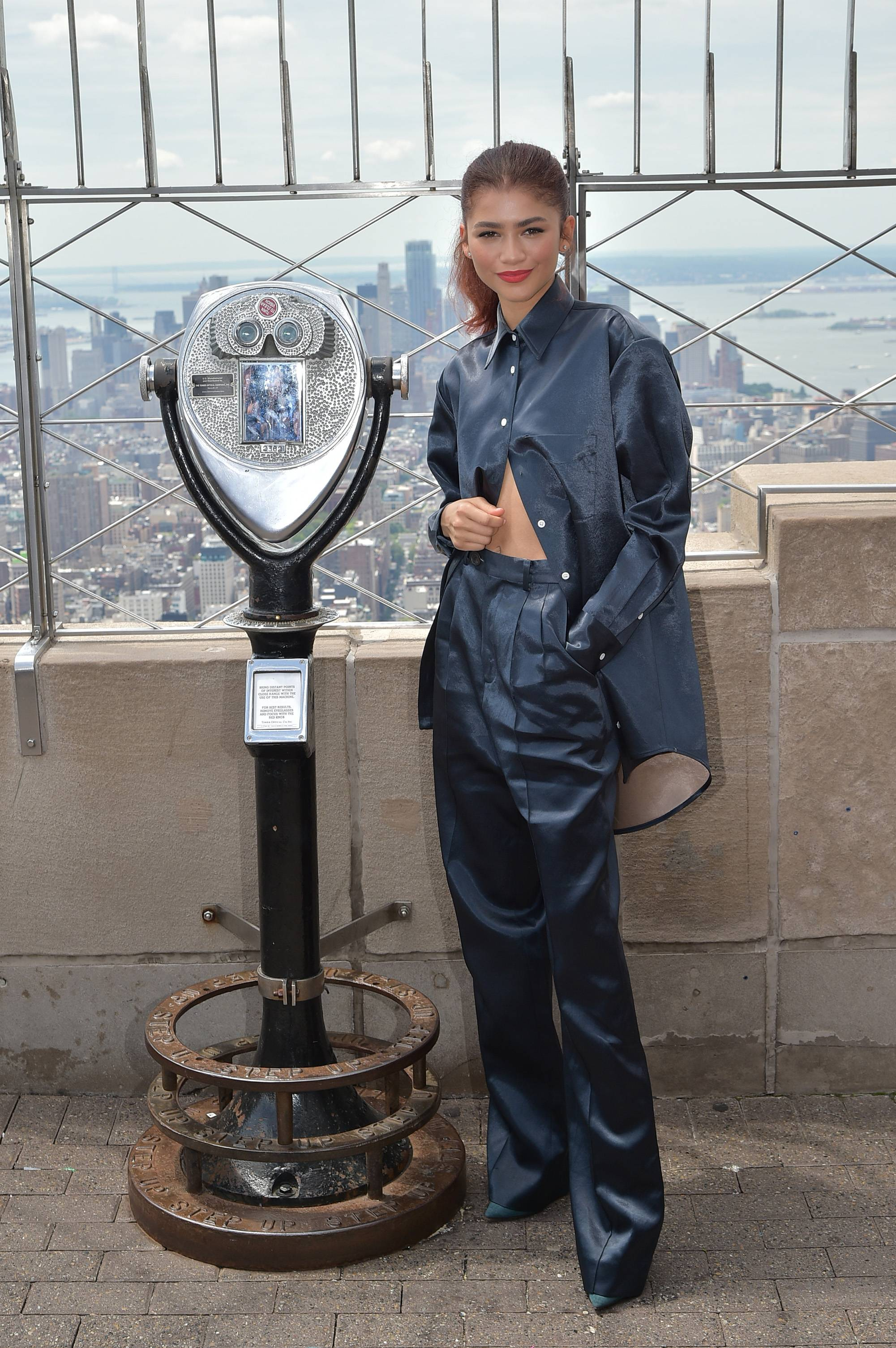 Zendaya Lights Up the Empire State - Looking fly in the concrete jungle! Zendaya wore a sleek, midnight blue,FW19 Peter Do bonded, satin pantsuit with the bottom buttons of the blouse unbuttoned while promoting her upcoming film at the Empire State Building.