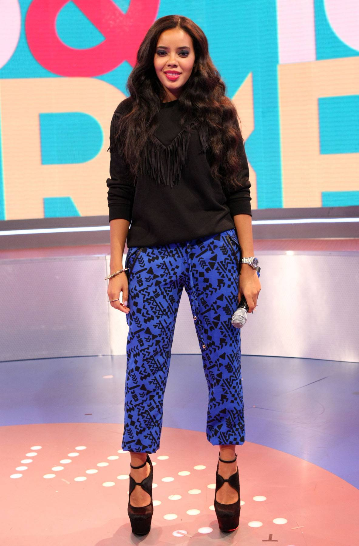 Armed and Ready - As always host Angela Simmons slays in a simple black top and patterned royal blue pants.(Photo: Bennett Raglin/BET/Getty Images for BET)
