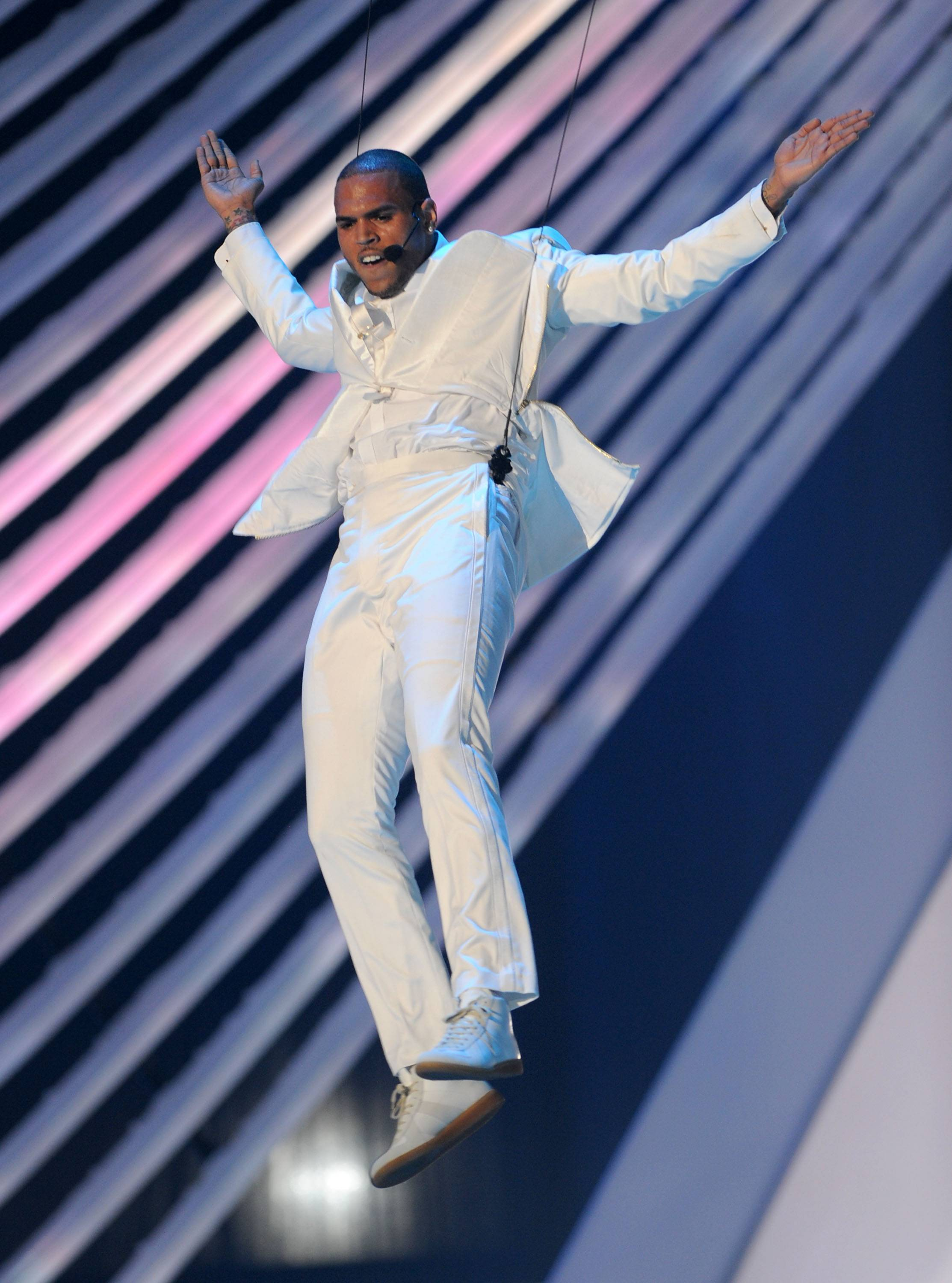 """2011 MTV Video Music Awards - A year after Breezy literally embodied MJ at the BET Awards, he put on another killer performance at the 2011 MTV Music Video Awards. Brown kept the crowd fully entertained with a Cirque Du Soleilinspired performance,featuring high-flying table jumping and impeccable choreography. He danced to a medley of hits including hits from Wu-Tang Clan, Nirvana and his own songs """"Yeah 3X"""" and """"Beautiful People."""" (Photo: Kevin Winter/Getty Images)"""