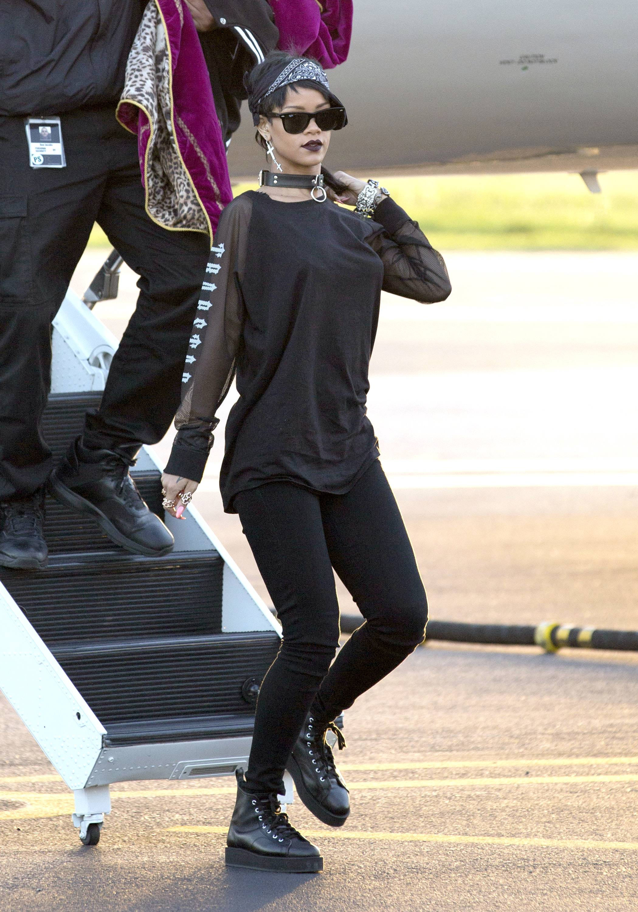 """Rih-Rih Goes Dark - """"Ghetto goth,"""" a modern mash-up of '80s and '90s urban wear (hoodies, snapbacks and Jordans), '90s grunge (layering and rugged details) and gothic styles (statement accessories, head-to-toe black and subtle shine) is gaining steam in fashion circles, with Rihanna leading the push. Keep reading to see how Rih-Rih rocks this rebellious look. By Britt Middleton  We first noticed the singer?s transition in late August, when she debuted a rocker-inspired mullet. We admit we?re still getting used to her new look, but we give her props for keeping us on our toes, as she did recently in a black and mesh top, bandana and leather dog collar choker.  (Photo: FameFlynet, Inc)"""