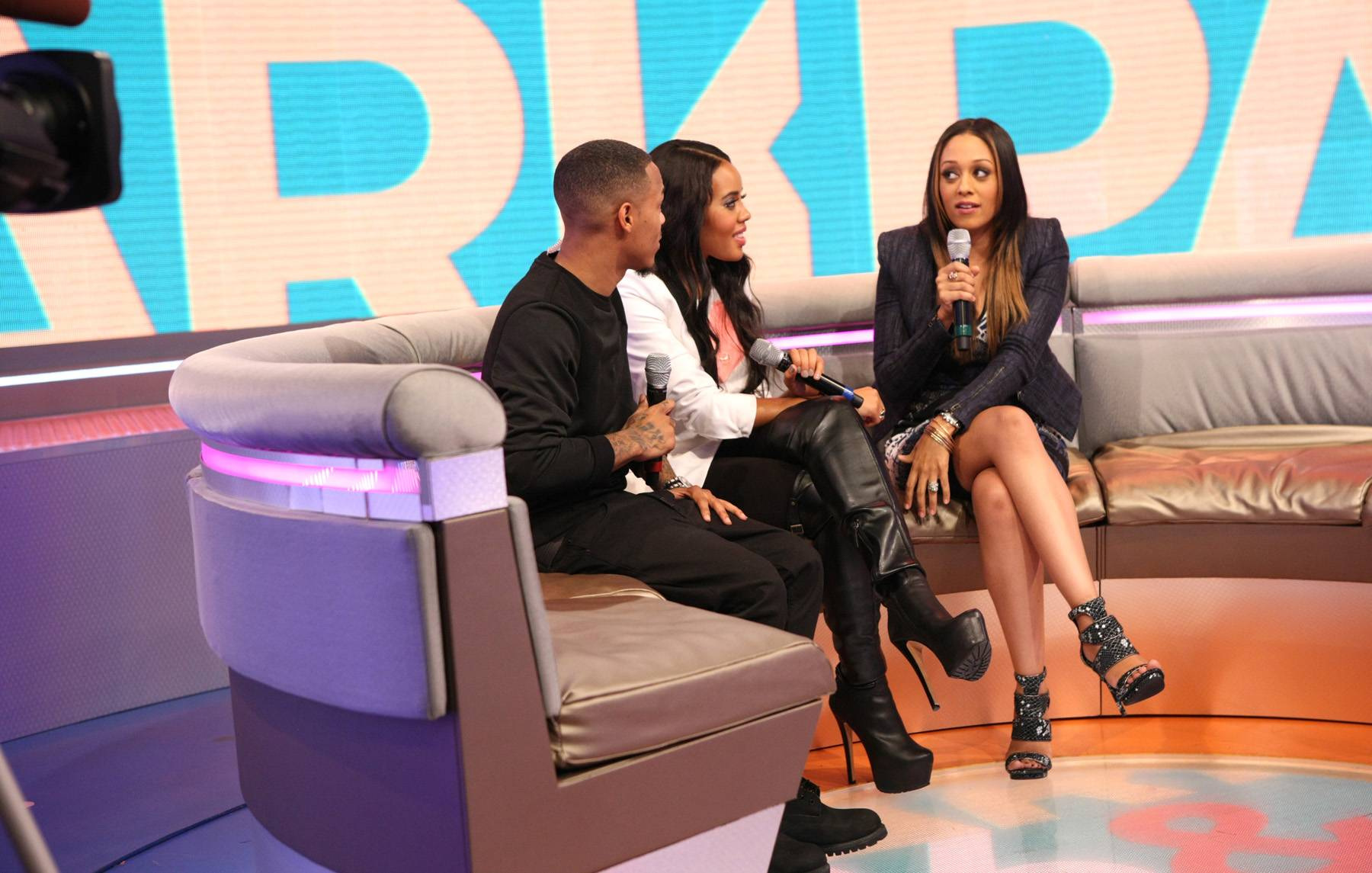 Let Me Think - Bow Wow and Angela Simmons relax as actress Tia Mowry-Hardrict thinks about a question.(Photo: Bennett Raglin/BET/Getty Images for BET)