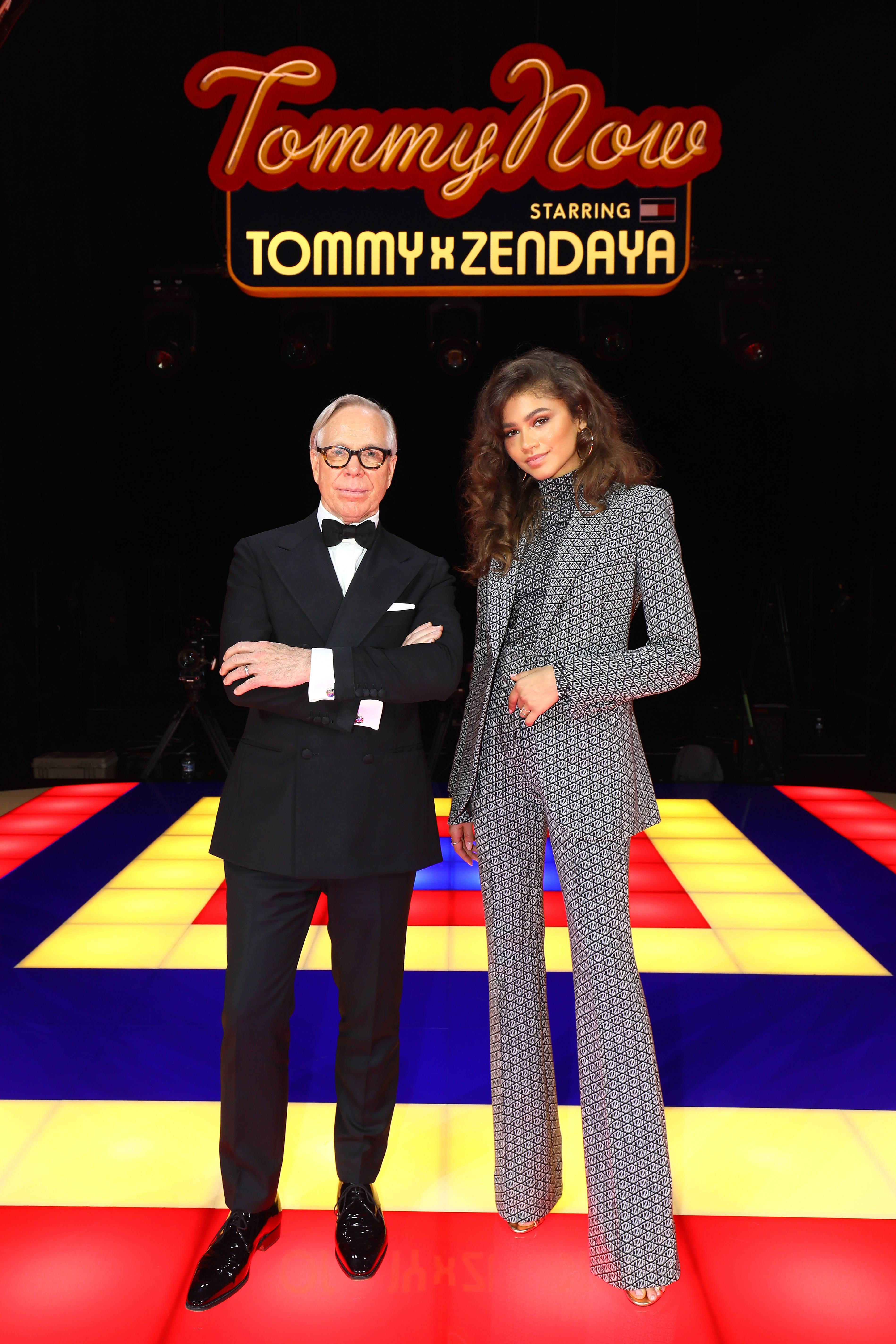 Runway Slay - After her iconic Tommy X Zendaya runway show during Paris Fashion Week, Zendaya posed with Tommy Hilfiger with one of the custom pieces from their 70s inspired collection!(Photo: Tim P. Whitby/WireImage)