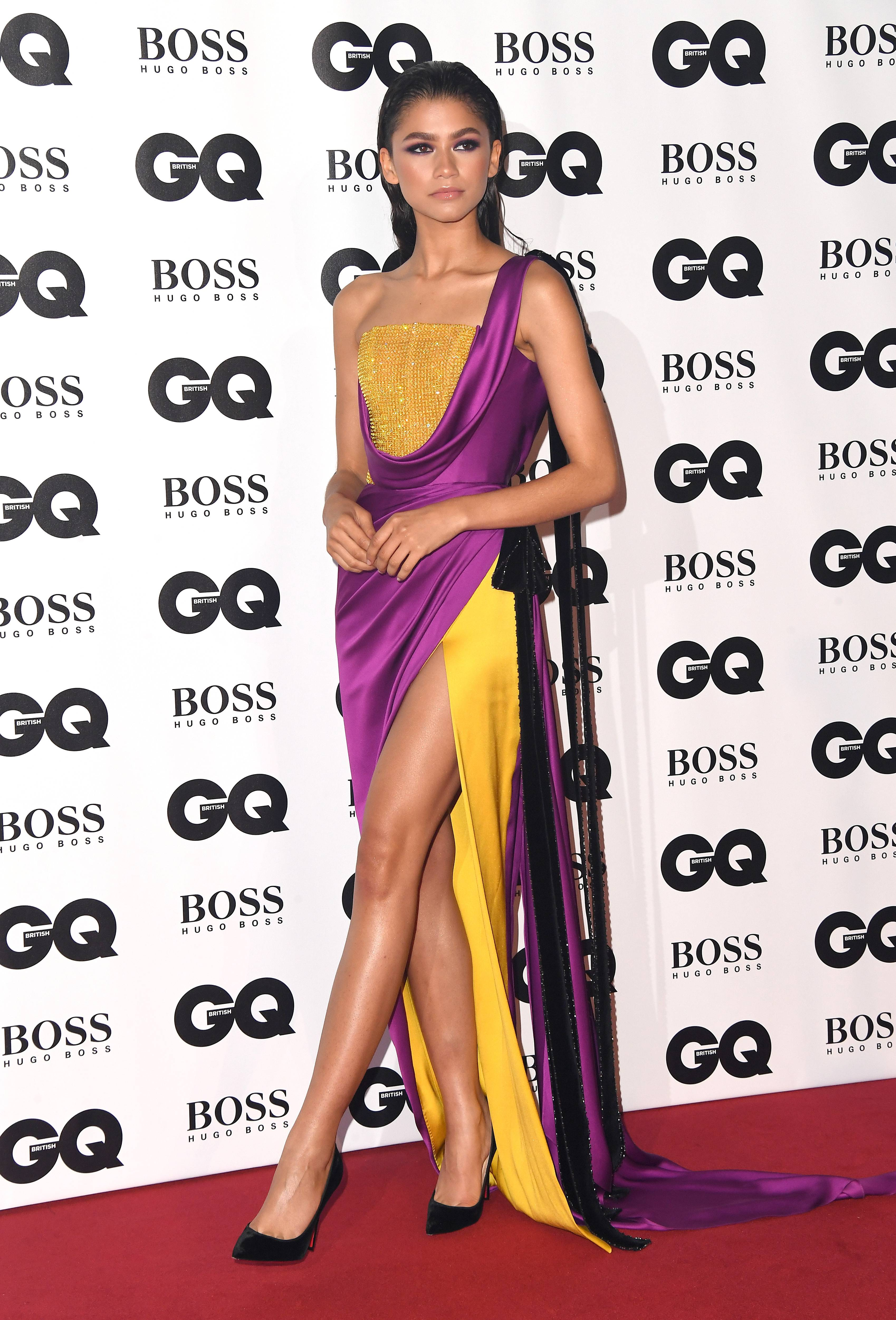 Princess Jasmine Vibes - Not only does she slay red carpets, but she does her own makeup, too! Daya was breaking necks at the GQ Men Of The Year Awardsin this marigold and fuschia gown with a velvet bow and beaded bustier with one sleeve fromRalph and Russo and blackLouboutinpumps ($695). (Photo: Karwai Tang/WireImage)