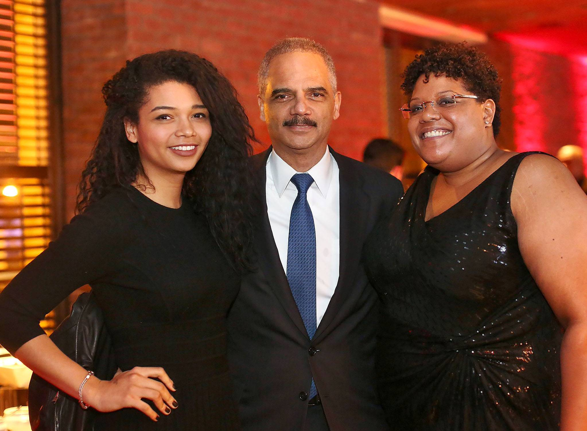 Holding a Piece of History - Attorney General Eric Holder and his guests share a warm embrace while taking a picture.  (Photo: Phelan Marc/BET)